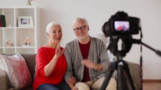 technology, blogging and people concept - happy smiling senior couple with camera recording video message at home