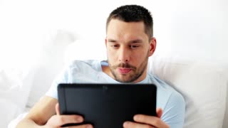 technology, communication and people concept - happy man with tablet pc computer having video chat in bed at home