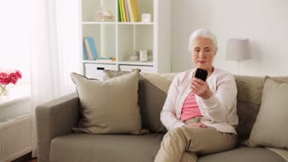 technology, old age and people concept - happy senior woman with smartphone taking selfie at home