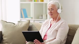 technology, old age and people concept - happy senior woman with tablet pc computer and headphones listening to music at home
