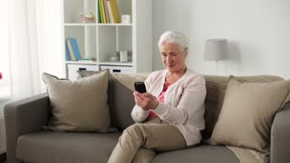 technology, old age, communication and people concept - happy senior woman with smartphone texting message at home