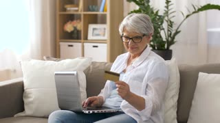 technology, online shopping and people concept - happy senior woman in glasses with laptop computer and credit or bank card at home