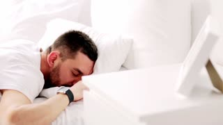 technology, sleeping and people concept - man with smartwatch waking up in bed at home