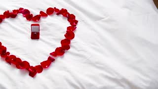 valentines day, proposal and romantic date concept - bed decorated with heart made of red petals and diamond engagement ring in gift box