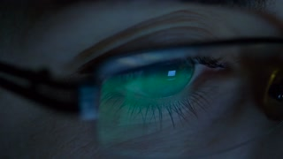vision, business and education concept - close up of woman eyes in glasses looking at computer screen in darkness