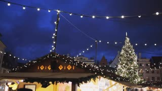 winter holidays, celebration and cityscape concept - illuminated christmas tree at old tallinn town hall square and city fair