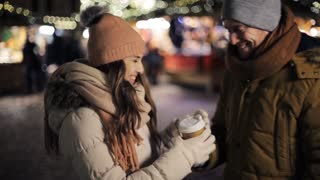 winter holidays, hot drinks and people concept - happy young man bringing coffee in disposable paper cup for his woman at christmas market in evening