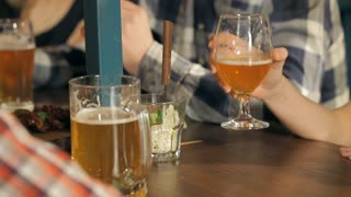 A bar table with mugs, glasses of beer and snacks. Men and women are sitting, drinking, having fun. Weekends, holidays