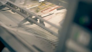 A conveyor for printing newspapers. A digital display shows the number of newspapers. There are fast moving parts, a loud noise is heard. Old machines for offset printing are working and releasing the