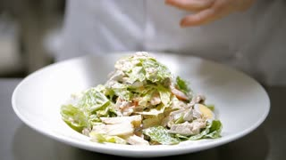 A cook is preparing Caesar salad. Video shows a plate with salad. The cook is laying an egg and sprinkling the salad with seasoning. Close-up shot