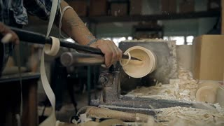 A craftsman holds a chisel and handles a rotating work piece on the machine. Sawdust is flying, you can hear a loud noise. In the end matreshka is made - a national Russian toy