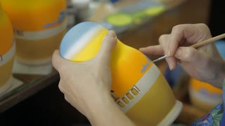 A craftsman is painting a national Russian doll with brushes and paints