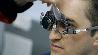 A doctor is checking a male patient's eyes. The man is trying on different lenses on each eye and saying how well he sees. The procedure is performed to make new glasses to improve the patient's