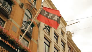 A flag of Amsterdam on an old building