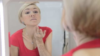 A girl is sitting in front of a mirror and concealing a pimple on her chin with the help of a corrector
