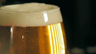 A glass of fresh light beer. There is white foam and bubbles striving upward in a glass