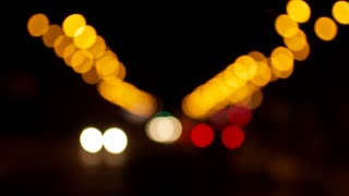 A great background. A blurred night road with lanterns and moving cars. Middle-sized colorful bokeh in the shot
