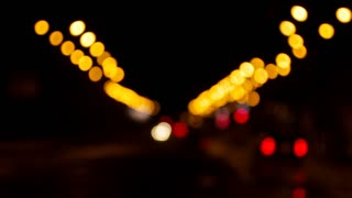A great background. A blurred night road with lanterns and moving cars. Small colorful bokeh in the shot