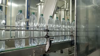 A large machine with rotating parts is holding bottles by the necks and pouring the water inside