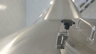 A large metal tank in which beer is being brewed. A brewer is unscrewing the valves to have a look at the process