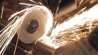A locksmith in the basement is laying pipes for water supply. He is sawing metal. Bright sparks are flying