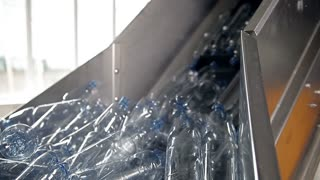 A lot of still empty bottles are moving on the conveyor at a bottling plant of mineral water