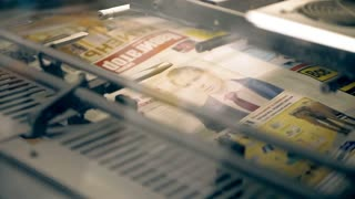 A machine is folding printed newspapers in a pile. There are fast moving parts, a loud noise is heard. Old machines for offset printing are working and releasing the circulation