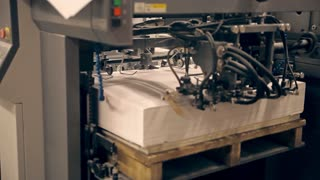 A machine is giving the paper for printing newspapers. There are fast moving parts, a loud noise is heard. Old machines for offset printing are working and releasing the circulation