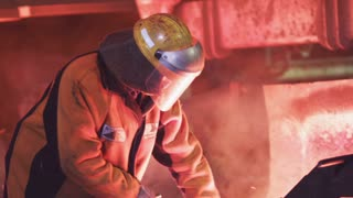 A man is checking the quality of molten metal