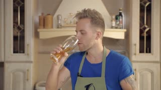 A man tries a beer from a glass that stood in the kitchen and understands that it is spoiled, goes to puke