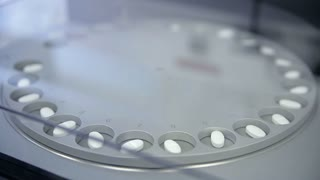 A metal circle with holes is rotating and aligning the tablets so that they were all directed to one side. Then it is moving medicines to packing in blisterpacks