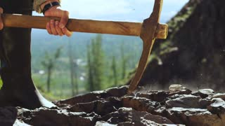 A miner is mining ore with a pickaxe