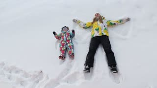 A mother and daughter dressed in bright warm jackets are playing on the snow in a cold winter