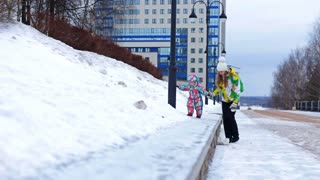 A mother and daughter dressed in bright warm jackets are walking on the snow in a cold winter