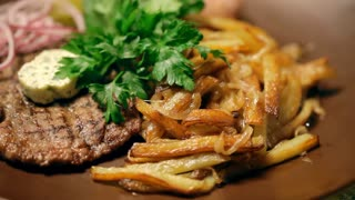 A national dish of Ukrainian cuisine. There are French fries, cutlets, parsley and the chopped onion on a brown plate. A close-up