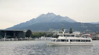 A passenger ship is sailing on the lake, mountains in the background