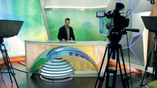 A presenter of the news tells the camera about the main events in sport, politics, economy, city, country, world, the Internet