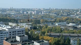 A typical town of Central Russia. The view from the top. There are low houses, trees, cranes