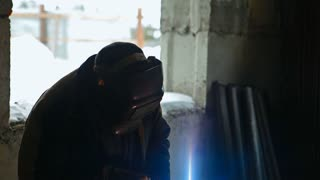 A welder in mask is welding metal rods for the construction of a high-rise building of brick. Sparks are flying and bright flashes are glowing