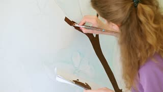 A white wall, the girl is beginning to draw a tree on it. First she is making sketches, and then she is filling the pattern with brown and green paints