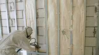 A worker in a mask and overalls warms the walls spraying polymer. A mixture of elements sticks to the surface, reducing sound and thermal transmittance. White polypropylene mixture is being fed