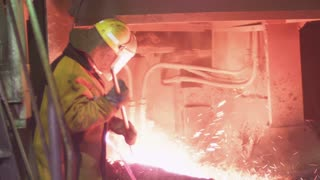 A worker is checking the quality of molten metal