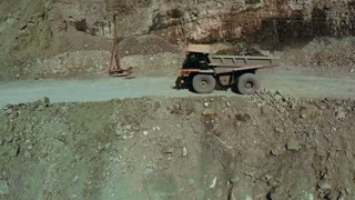 Aerial. A big truck is transporting ground in an open pit