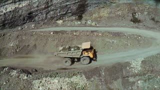 Aerial. A big truck is transporting ground in an opencast mine