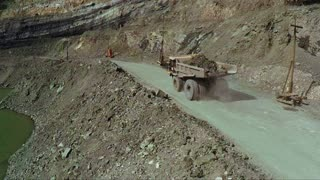 Aerial. A big truck is transporting ore in an open pit