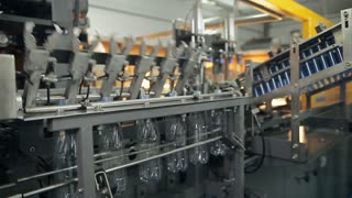 An automatic arm is getting just made plastic bottles out of the oven and sending them down the pipeline