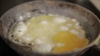 An egg is being fried on an old pan. Due to old age and poor quality of the pan it's getting burnt and sticking to the pan