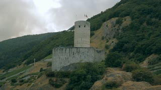 An old fortress with flags on the mountain