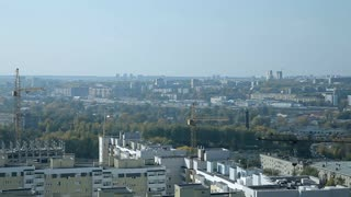 An ordinary city in the Central part of Russia. A view from the top. There are low houses, trees, cranes
