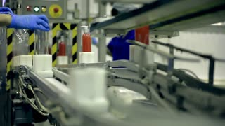 Automatic conveyor line driven by motors. Plastic bottles with dispensers are moving on the line. The line produces shower gels, liquid soaps, shampoos and other means of personal hygiene. Workers in